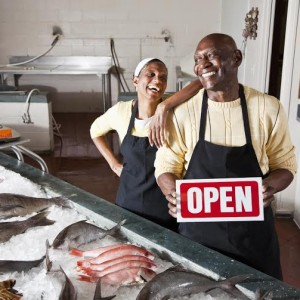 Small business owners - Senior African American couple selling fresh fish.